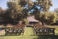 Winery wedding, wood chairs with garlands of greenery on backs winery vineyard outdoor wedding