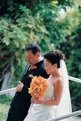 Bride in a strapless dress with father in a black tuxedo