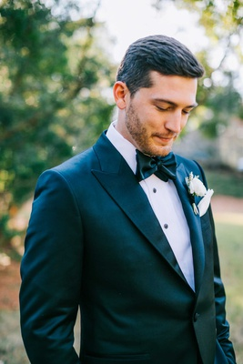 dapper groom with bow tie and white boutonniere