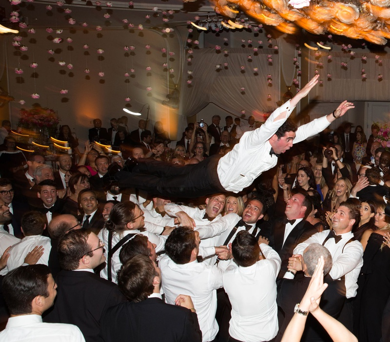 Groom without tuxedo jacket body surfing crowd surfing at wedding reception during hora jewish