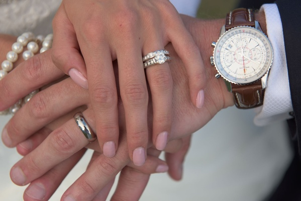 Bride's diamond engagement ring and men's watch with leather band polished men's band