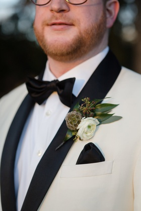 unique boutonniere ideas, boutonniere with a white ranunculus, scabiosa pod, leaves