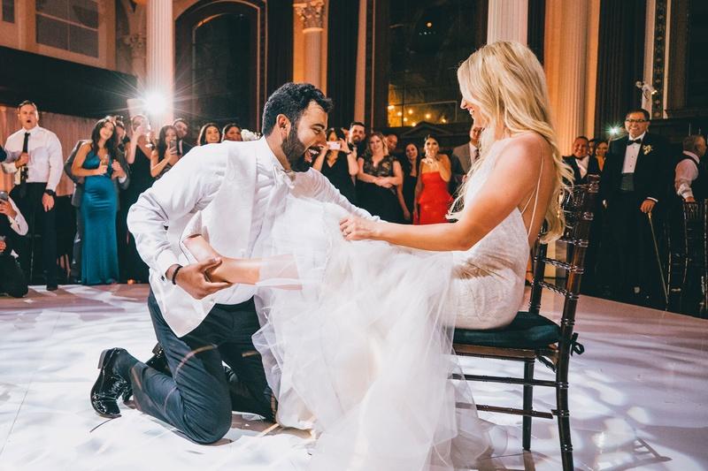 bride sitting on black chair white dance floor groom removing garter from bride leg garter toss