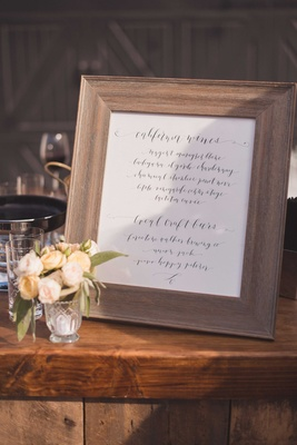 Calligraphy sign by Laura Hooper in rustic wood frame on wood bar at outdoor winery wedding