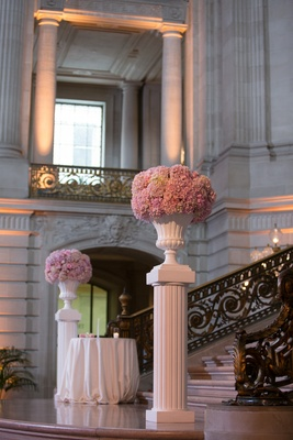 White risers with white urns filled with pink hydrangeas at bottom of City Hall stairs