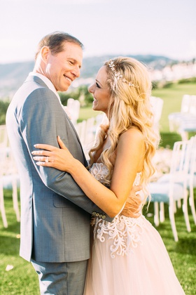 bride in custom trish peng wedding dress blush undertones grey suit for groom ceremony portrait
