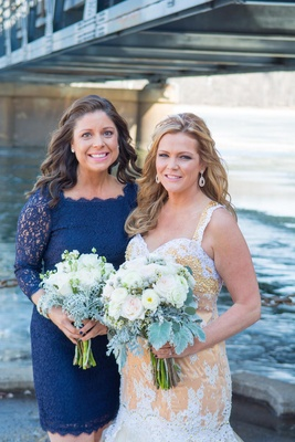 Bride in gold wedding dress with bridesmaid in lace blue dress