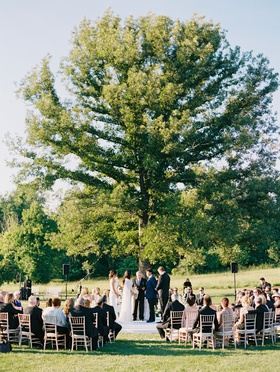 Bride and groom at outdoor wedding ceremony guests seated in the round under tall tree