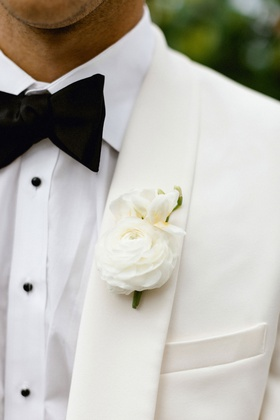 wedding attire for groom white suitsupply tux with black bow tie white ranunculus flower boutonniere