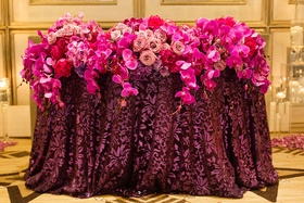 pink and purple floral arrangements orchids roses linens reception cascading