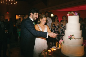 bride and groom cutting into five layer wedding cake fresh flowers