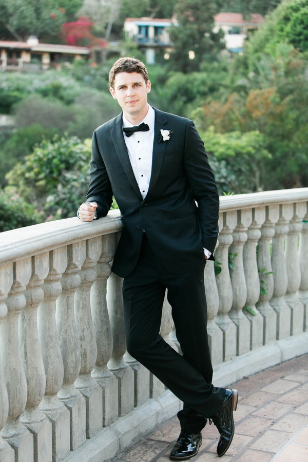 groom in a classic black tuxedo with black bow tie