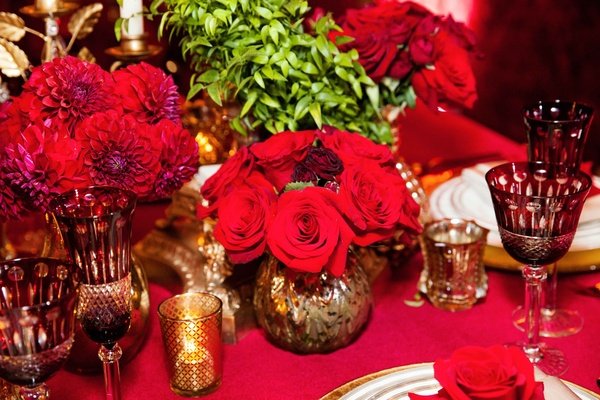 red mums and roses in gold vases surround the centerpiece