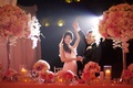 Asian bride and groom dance at wedding with pink flowers