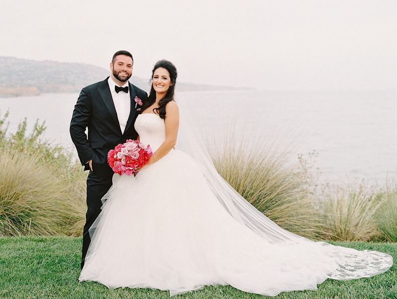 bride and groom with bright pink bouquet pose on cliffside overlooking the ocean