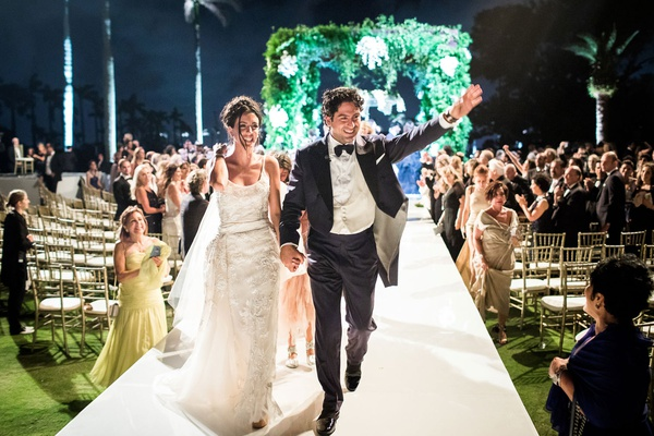 wedding couple on raised aisle walking hand in hand up aisle husband wife lighting night ceremony