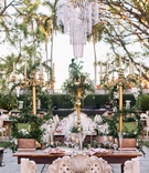 sweetheart table with carved bench, three tall gold candelabra with greenery, chandelier above