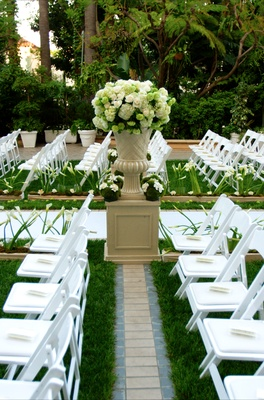 White ceremony chairs and flower arrangements along aisle