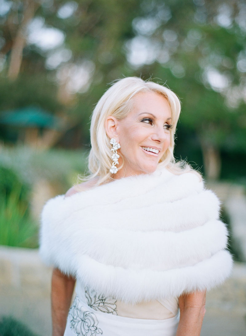 Mother of bride in J Mendel dress with white fur stole and flower motif earrings