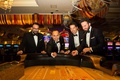 groom and groomsmen in classic tuxedos at gambling table in casino