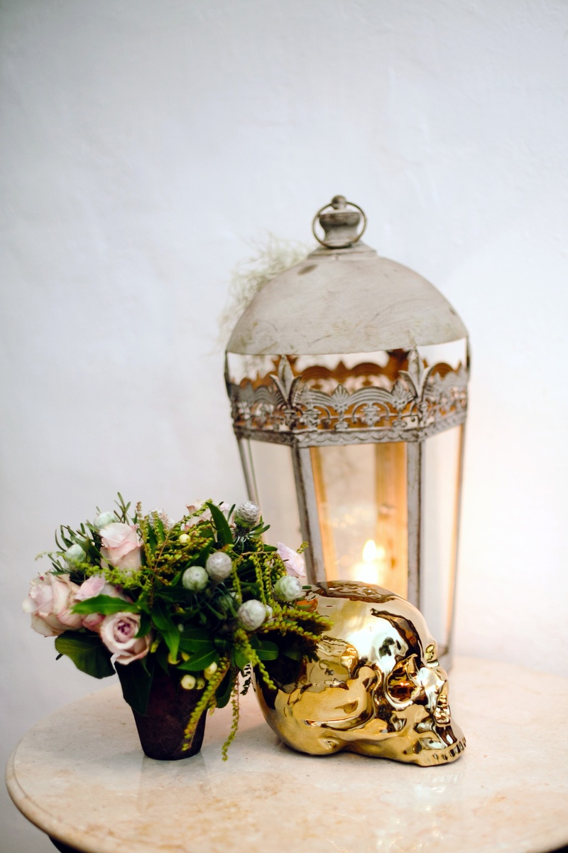 White lantern with pink rose arrangement and metallic gold skull
