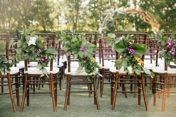 wedding ceremony dark wood chairs white cushions green leaves greenery purple yellow flowers
