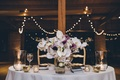 Wedding reception rustic design white and purple orchid flower arrangement wood beams twinkle lights
