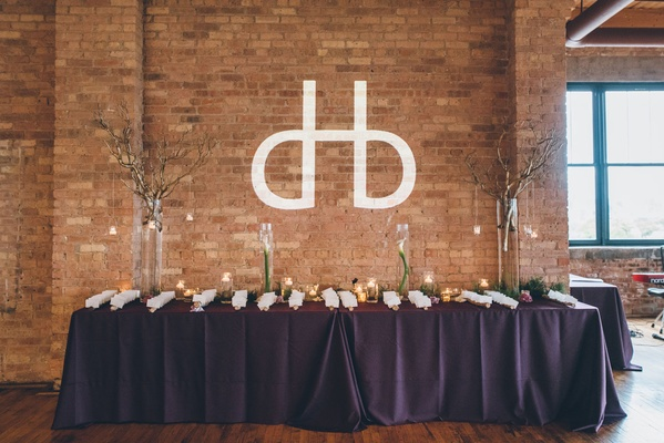 Modern wedding monogram on brick wall over table decorated with flowers branches and escort cardsq