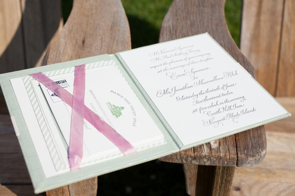 Green book cover with calligraphy invitation and cards