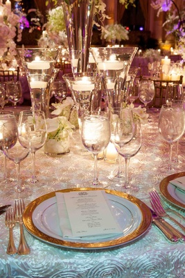 Wedding reception table with floating candles and small arrangements of white orchids