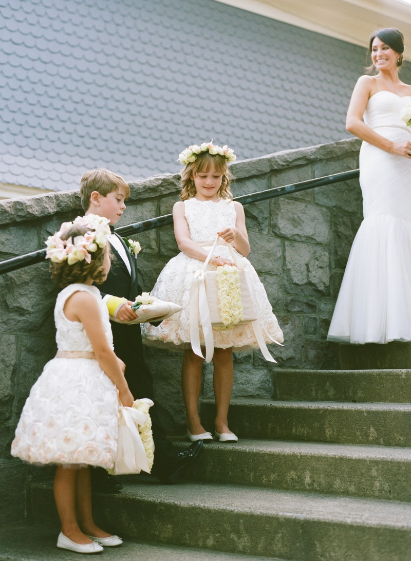 Flower girls with rose dresses and flower crowns on stairs