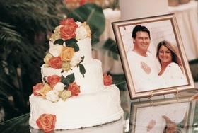 White wedding cake with orange and white roses
