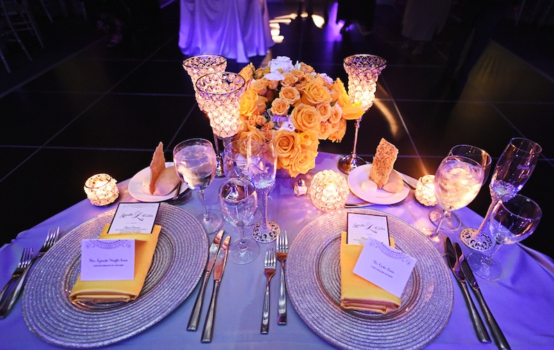 Wedding reception table with silver chargers, gold napkins, yellow roses, white hydrangeas, candles