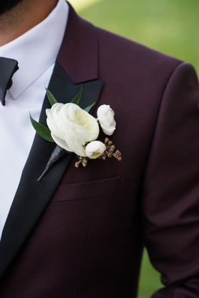 Groom in colored suit jacket black lapels burgundy suit white ranunculus boutonniere