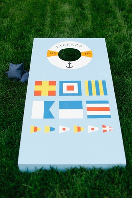 Waterfront wedding with nautical-themed blue cornhole board on green lawn