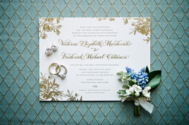 White wedding invitation with gold foil flower print and calligraphy boutonniere wedding rings