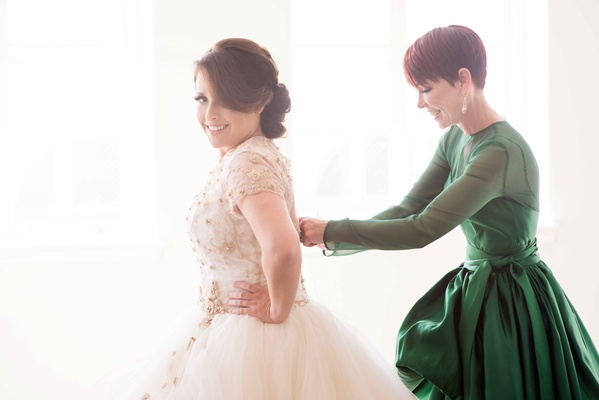 Mother of bride helping daughter put on wedding dress in designer green dress with long sleeves