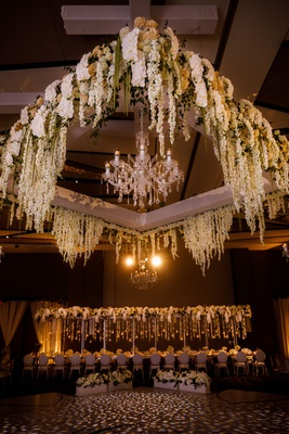 wedding reception ballroom dance floor white flowers greenery chandelier overhead flower arrangement
