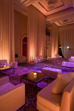 Wedding reception lounge area with plush seating draped with sheer pink fabric