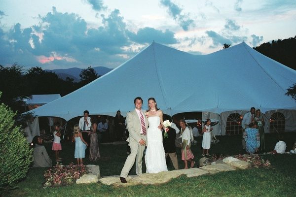 Newlyweds outside by tented structure