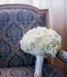 White bridal bouquet with crystal and satin wrap on chair