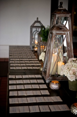 Wood escort card tables with lanterns, pillar candles, white & light pink roses at elegant, rustic