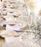 silver sequin tablecloths and clear chargers on reception table