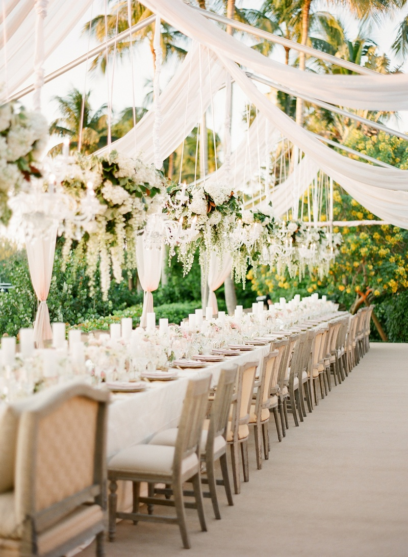 Wedding reception with a long table under suspended floral arrangements and chandeliers & Reception Décor Photos - Romantic Open-Air Tent + Floral ...
