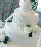White buttercream cake with white roses and monogram