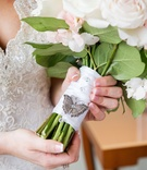 Bride holding ribbon-wrapped flowers with sparkles