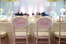 Head table with bride and groom chairs pink sign with ivory flower petals around border flower petal