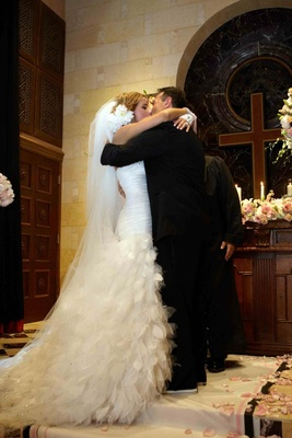 Bride and groom kissing in front of cross