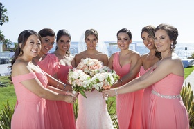 Bride in strapless wedding dress with bridesmaids in different dresses in coral with blush bouquets