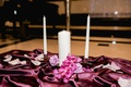 Unity candle with inscription on table with purple linens and flower petals church ceremony Baptist